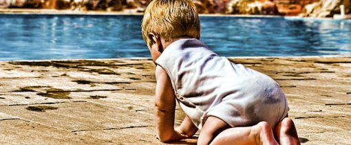 Pool Safety baby crawling to the edge of a swimming pool